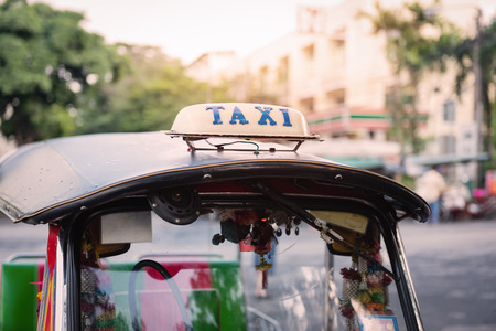three wheeler: Taxi sign on roof top car waiting for passenger on street at bangkok in thailand
