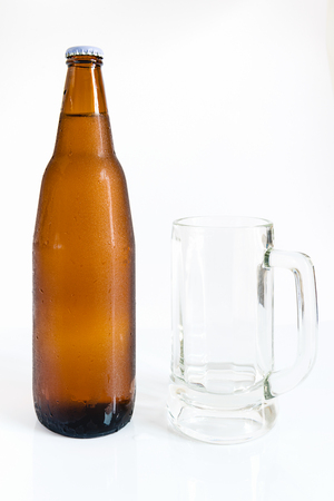 dew cap: Bottle of beer with drops on white background with empty glass Stock Photo