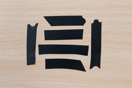 gaff: Set of different black adhesive duct tape pieces on wooden background Stock Photo