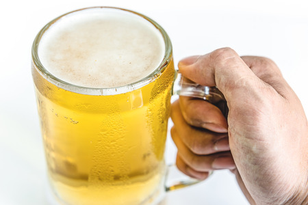 un bottled: man hand holdin frosty glass of light beer for drinking on a white background