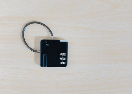 stainless steal: little black combination padlock on wooden background Stock Photo