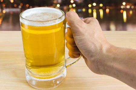 un bottled: man hand holding frosty glass of light beer for drinking on wooden with blurred background