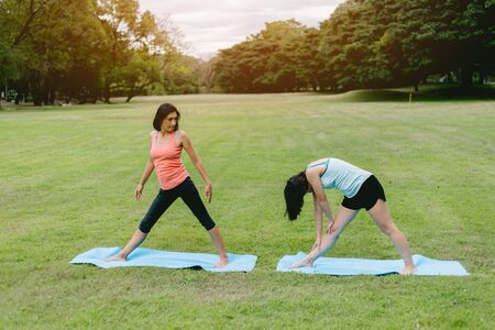 Woman do yoga and relaxation in garden. Woman exercising vital and meditation for fitness lifestyle at the nature background. Concept Yoga