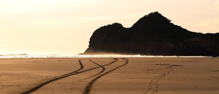 headland: Beach with car tracks and silhouette of headland Stock Photo