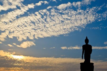 Silhouette of buddha statue with sunset photo