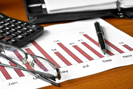 printed matter: Bar graph with glasses, ballpoint pen and calculator Stock Photo