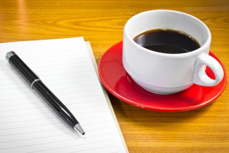Note book and pen with a cup of coffee photo