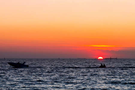 sunset at the sea with silhouette jet ski photo