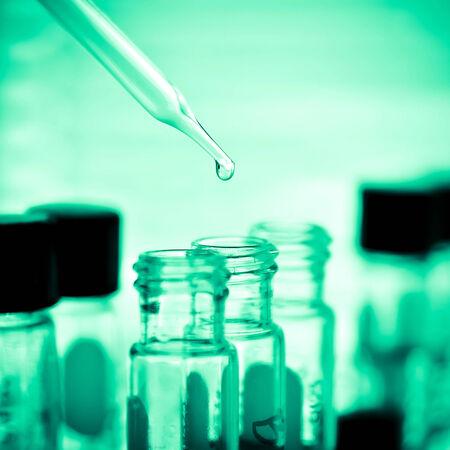 laboratory technician: Dropping liquid to test tube, Laboratory
