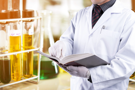 Scientist reading text book with laboratory background