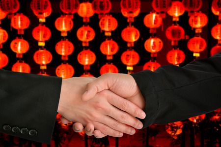 chiness: business handshake with Chiness lamp background