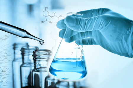 Flask in scientist hand and laboratory glassware background