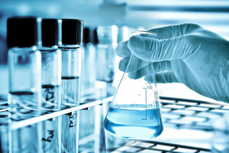 Kolf in wetenschapper hand en laboratoriumglaswerk achtergrond Stockfoto