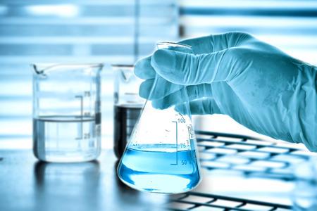 Kolf in wetenschapper hand en laboratoriumglaswerk achtergrond Stockfoto - 45720420