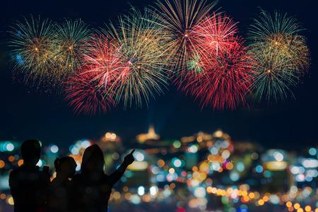 fuegos artificiales: La familia feliz se ve celebración de fuegos artificiales en el cielo nocturno Foto de archivo