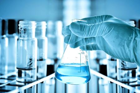 experimento: Frasco de científico mano con el fondo de laboratorio Foto de archivo