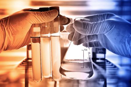 investigador cientifico: Frasco en la mano con el fondo científico de vidrio de laboratorio Foto de archivo