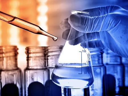laboratorio: Frasco en la mano con el fondo científico de vidrio de laboratorio Foto de archivo