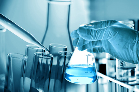 biotecnologia: Frasco en la mano con el fondo científico de vidrio de laboratorio Foto de archivo