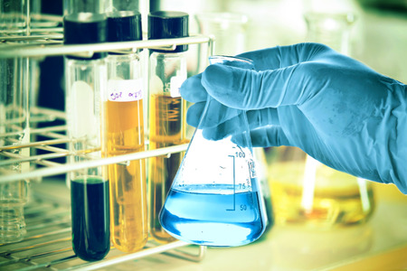 boiling tube: Flask in scientist hand in laboratory Stock Photo