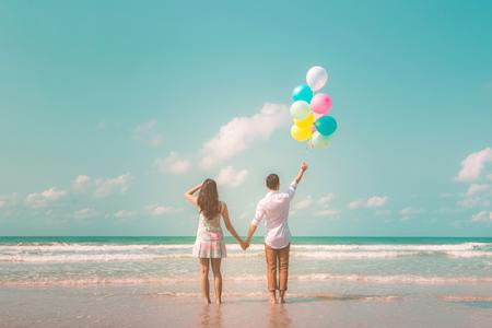 Portrait de couple de jeunes hipsters mariés heureux dans des vêtements vintage branchés debout ensemble sur la plage avec des ballons. Journée d'été ensoleillée. Tonalités de couleurs pastel