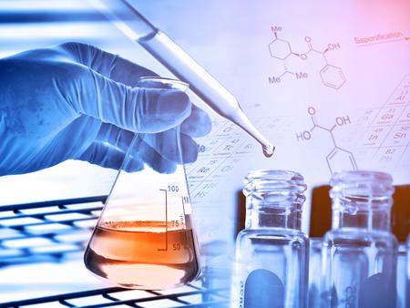 Fles in wetenschapperhand met laboratoriumachtergrond Stockfoto - 69748287