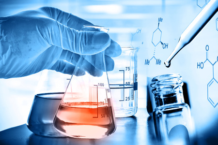 Flask in scientist hand with laboratory background