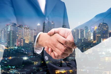 Double exposure of handshake and city