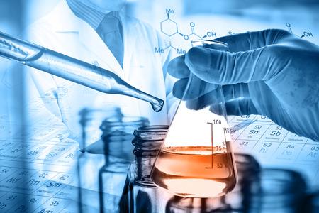 Fles in wetenschapperhand met laboratoriumachtergrond Stockfoto - 76819074