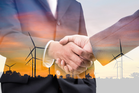 Double exposure of handshake and silhouette of wind turbine at sunset Stock Photo