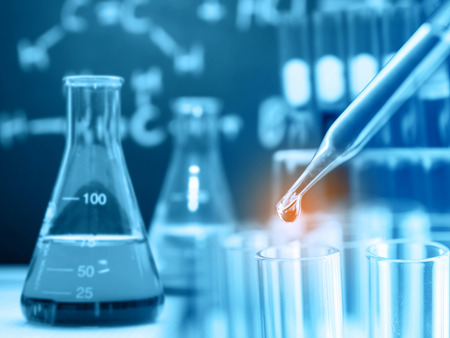 Dropping chemical liquid to test tube with laboratory glassware background Stock Photo