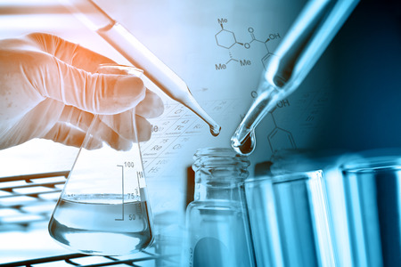 Flask in scientist hand with laboratory glassware background Stock Photo - 91445922