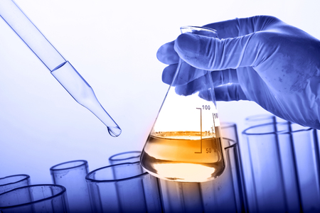 Dropping chemical liquid to test tube with flask in scientist hand