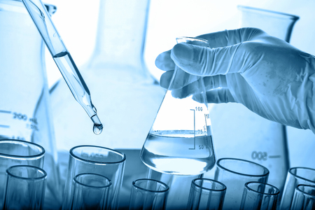 Laboratory research and development concept, dropping liquid to test tubes with lab glassware background.