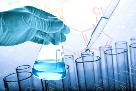 Flask in scientist hand with dropping liquid to test tube, Chemical, scientific research and development concept Stock Photo