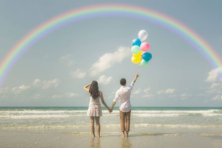 Portrait of couple of young happy married hipsters in trendy vintage clothes standing together on the beach with balloons and rainbow Pastel colors tone Imagens