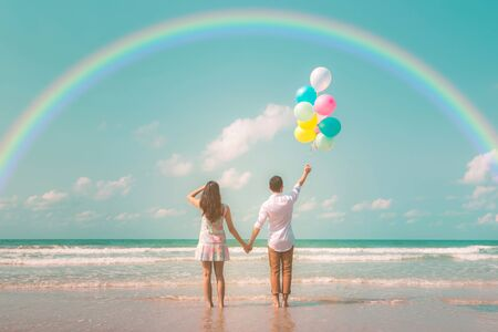 Portrait of couple of young happy married hipsters in trendy vintage clothes standing together on the beach with balloons and rainbow Pastel colors tone Stockfoto - 133407296