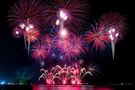 Erstaunliches buntes Feuerwerk für die Feiernacht auf dem Meer mit unscharfem Stadtnachthintergrund. Feiern Sie Weihnachten und Countdown zum Konzept des guten Rutsch ins Neue Jahr. Standard-Bild