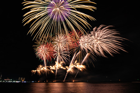 Amazing colorful fireworks display for celebration night on the sea with blur city night background. Celebrate on Christmas and countdown to happy new year concept. 스톡 콘텐츠 - 122891578