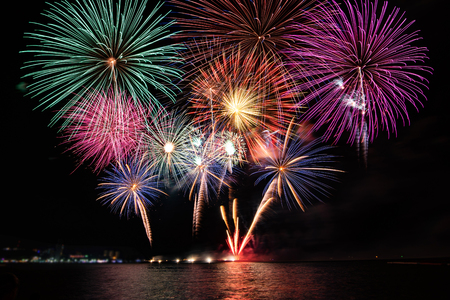 Amazing colorful fireworks display for celebration night on the sea with blur city night background. Celebrate on Christmas and countdown to happy new year concept. 스톡 콘텐츠