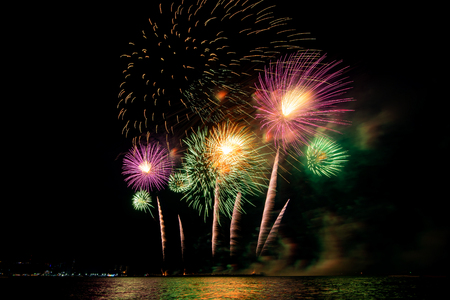 Amazing colorful fireworks display for celebration night on the sea with blur city night background. Celebrate on Christmas and countdown to happy new year concept. 스톡 콘텐츠 - 122891594