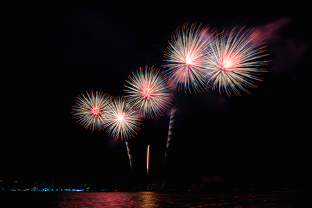 Amazing colorful fireworks display for celebration night on the sea with blur city night background. Celebrate on Christmas and countdown to happy new year concept. 스톡 콘텐츠 - 122891596
