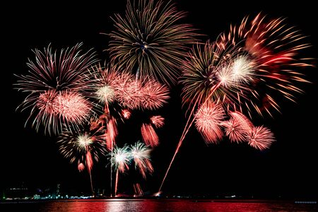 Amazing beautiful colorful fireworks display on celebration night, showing on the sea beach with multi color of reflection on water Stockfoto - 132149348