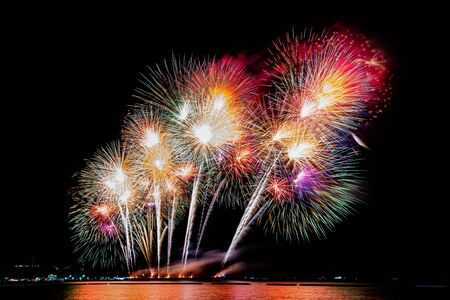 Amazing beautiful colorful fireworks display on celebration night, showing on the sea beach with multi color of reflection on water Stockfoto - 132149257