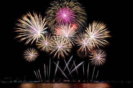 Amazing beautiful colorful fireworks display on celebration night, showing on the sea beach with multi color of reflection on water Stockfoto - 132149329