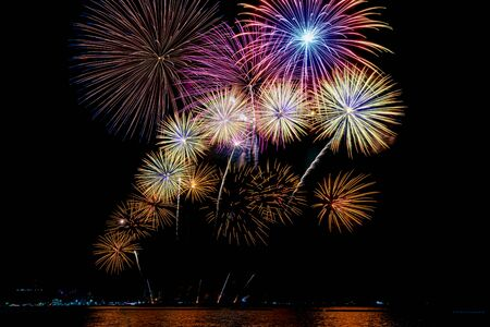 Amazing beautiful colorful fireworks display on celebration night, showing on the sea beach with multi color of reflection on water Stockfoto - 132148802