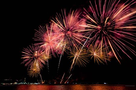 Amazing beautiful colorful fireworks display on celebration night, showing on the sea beach with multi color of reflection on water Stockfoto - 132149057