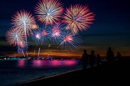 Amazing beautiful colorful fireworks display on celebration night, showing on the sea beach with multi color of reflection on water Stockfoto - 132148776