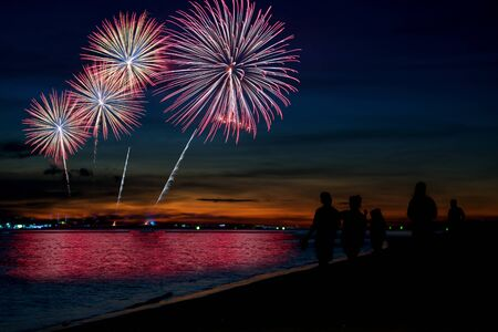 Amazing beautiful colorful fireworks display on celebration night, showing on the sea beach with multi color of reflection on water Stockfoto - 132148374