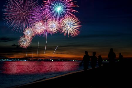 Amazing beautiful colorful fireworks display on celebration night, showing on the sea beach with multi color of reflection on water Stockfoto - 132148091